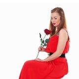 Elegantes schönes Mädchen in einem roten Kleid mit einer Rose Stockfotos