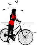 Elegantes Schattenbild des Pinupmädchens auf einem Fahrrad Lizenzfreie Stockbilder