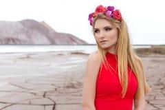 Elegantes schönes sexy Mädchen in einem Kranz von Blumen mit hellem Make-up in der Wüste Stockfotos