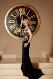 Elegantes Schwarzkleid Dame in Mode lang, das vor Wanduhr aufwirft Stockbild