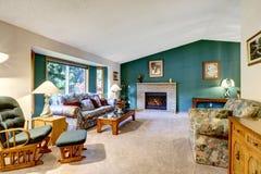 Elegantes weißes und grünes Wohnzimmer Klassisches amerikanisches Design: Ziegelsteinkamin, Schaukelstuhl und buntes Sofa lizenzfreie stockfotografie