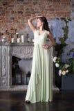 Elegantievrouw in lange beige kleding In binnenland Royalty-vrije Stock Afbeeldingen