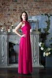 Elegantievrouw in lange roze kleding In binnenland Royalty-vrije Stock Foto