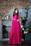 Elegantievrouw in lange roze kleding In binnenland Stock Foto's
