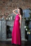 Elegantievrouw in lange roze kleding In binnenland Royalty-vrije Stock Foto's