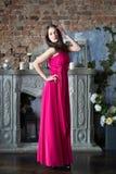 Elegantievrouw in lange roze kleding In binnenland Stock Foto