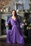 Elegantievrouw in lange violette kledingszitting op stoel binnen Stock Foto