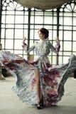 Elegantievrouw met vliegende kleding in paleisruimte royalty-vrije stock afbeeldingen