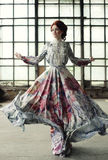 Elegantievrouw met vliegende kleding in paleisruimte Stock Afbeeldingen