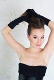 Elegantievrouw in zwarte handschoenen en kleding Houdt haar haar Stock Afbeeldingen
