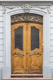 Elegant carved wooden door with ornament door frame. An elegant carved light brown wooden door with ornament grey frame and wall Stock Image