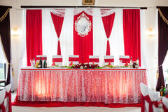 Elegantly catered wedding reception hall with red ribbons on lux. Ury white chairs and marble floor Stock Photos