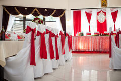 Elegantly catered wedding reception hall with red ribbons on lux Stock Photo