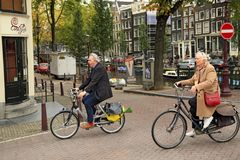 An elegantly dressed elderly couple riding the bicycles. Amsterdam, Netherlands. An elegantly dressed elderly couple riding the bicycles in the historical center Royalty Free Stock Photos