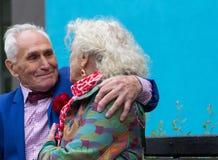 Elegantly dressed elderly man hugs elderly woman`s shoulders. Stock Images