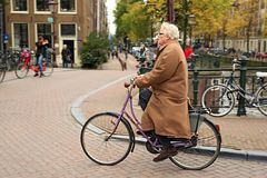 An elegantly dressed elderly man riding a bicycle. Amsterdam, Netherlands. An elegantly dressed elderly man riding a bicycle in the historical center. Bridge Stock Photography