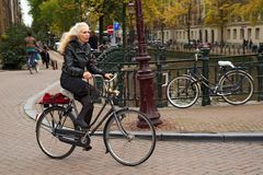 An elegantly dressed elderly woman riding a bicycle. Amsterdam, Netherlands. An elegantly dressed elderly woman riding a bicycle in the historical center. Bridge Stock Photography