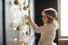 Elegantly dressed girl of 8-9 years with delight touches gold Christmas garlands. Christmas holidays. Elegantly dressed girl of 8-9 years with delight touches royalty free stock images