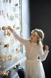 Elegantly dressed girl of 8-9 years with delight touches gold Christmas garlands Royalty Free Stock Photos