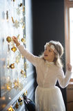 Elegantly dressed girl of 8-9 years with delight touches gold Christmas garlands. Christmas holidays. Elegantly dressed girl of 8-9 years with delight touches stock image