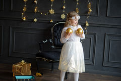Elegantly dressed girl of 8-9 years plays Christmas-tree decorations. Stock Photos
