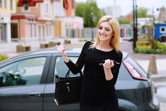 Elegantly dressed lady standing near car and holding car keys. Beautiful woman winks and smiles, pointing to the car. Elegantly dressed lady standing near car Royalty Free Stock Photos