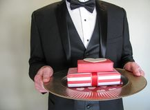 Mystery man in black tuxedo with Valentine's Day gifts. Elegantly dressed male, torso only, holding red and white gift-wrapped valentine presents on a gold Royalty Free Stock Image