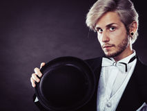 Elegantly dressed man holding black fedora hat Stock Photography