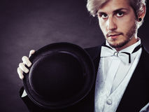Elegantly dressed man holding black fedora hat Stock Photo