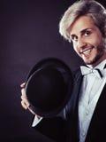 Elegantly dressed man holding black fedora hat Stock Photo
