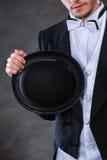 Elegantly dressed man holding black fedora hat. Tuxedo, male fashion, classical look concept. Elegantly dressed man holding black fedora hat. Studio shot on dark Royalty Free Stock Photo