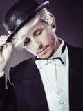 Elegantly dressed man wearing black fedora hat. Tuxedo, male fashion, classical look concept. Elegantly dressed man wearing black fedora hat. Studio shot on dark Royalty Free Stock Photography