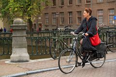 An elegantly dressed middle-aged woman riding a bike in the historical center. Amsterdam, Netherlands. An elegantly dressed middle-aged woman riding a bike in Royalty Free Stock Image
