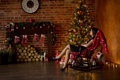 Elegantly dressed young woman sits in rocking-chair near Christmas-tree. Royalty Free Stock Photo