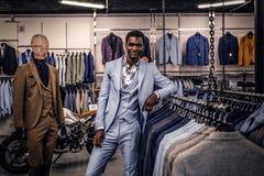Elegantly klädd afrikansk amerikanman som lutar på en skyltdocka i ett klassiskt menswearlager royaltyfri fotografi