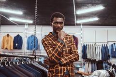 Elegantly klädd afrikansk man som poserar med handen på hakan, medan stå i ett klassiskt menswearlager royaltyfri foto