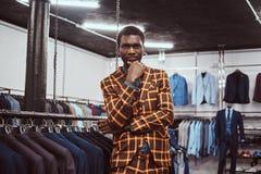 Elegantly klädd afrikansk man som poserar med handen på hakan, medan stå i ett klassiskt menswearlager royaltyfri fotografi