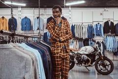 Elegantly klädd afrikansk man som poserar med handen på hakan, medan stå i ett klassiskt menswearlager arkivfoton