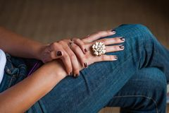 An elegantly pedicured ladies hand with marroon dark nail polish with a floral hand crafted luxury ring stock photo