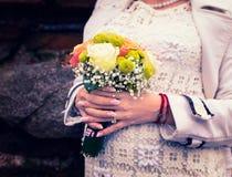 Elegantly rymmer påkläddkvinnan en bukett av blommor arkivfoto