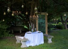 Romantic Dinner  in the Garden. An elegantly-set table for two in a wooded setting.  White table cloth, napkins, tall white tapers, crystal glasses.  Hanging Royalty Free Stock Images