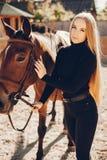 Elegants-Mädchen mit einem Pferd in einer Ranch stockfotos