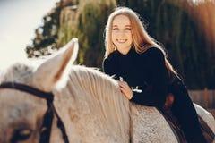 Elegants-Mädchen mit einem Pferd in einer Ranch lizenzfreies stockfoto