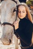 Elegants-Mädchen mit einem Pferd in einer Ranch lizenzfreie stockbilder