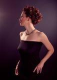 Elegantt högbarmat mognar kvinnan i svart åtsittande klänning royaltyfri foto