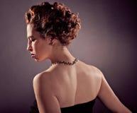 Elegantt högbarmat mognar kvinnan i svart åtsittande klänning royaltyfria foton
