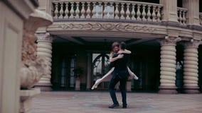 Elegantt koppla ihop Den unga mannen cirklar i händerna av en flicka i bakgrunden av slotten arkivfilmer