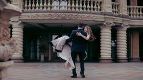 Elegantt koppla ihop Den unga mannen cirklar i händerna av en flicka i bakgrunden av slotten stock video