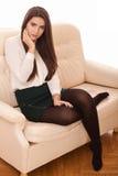 Elegantt kvinnasammanträde på sofaen fotografering för bildbyråer