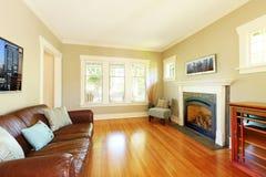 Elegantt vardagsrum med spis- och lädersofaen med beige väggar. fotografering för bildbyråer